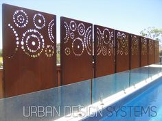 Laser cut screening - Dots (custom) This twelve panel decorative feature wall made of corten weathering steel provides artistic privacy over their pool and deck area. Each panel is independently installed on hidden posts fixed in-ground, leaving a precision gap between each panel. The setting sun casts wonderful shadows across the area.