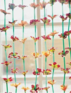 Handmade window curtain made of straws and flowers, plastic recycling ideas for home decorating.