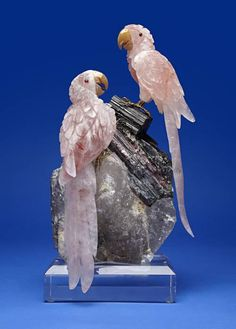 By Peter Mueller Carved from quartz having red inclusions, with agate beaks and tongues, two cabochon garnet eyes, raised on gold vermeil feet. The pair perches upon a massive tourmaline in quartz base which rests upon a custom lucite base. Height 16in