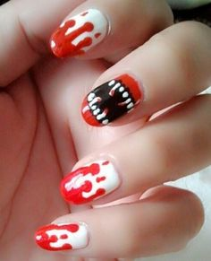 Try out this bloody mouth Halloween nail art design. Give terror to your nails by painting a mouth with bloody fangs along with splattered blood all over your other nails for effect.
