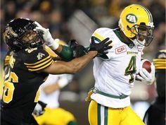 Edmonton Eskimos slotback Adarius Bowman (4) fends off Hamilton Tiger-Cats defensive back Johnny Adams (26)during the first-half of CFL football action in Hamilton on Friday, October 28, 2016.