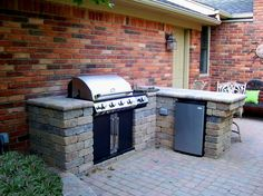 Brick Outdoor Kitchen with grill and mini fridge built into existing patio - Michigan Landscape Projects and Designs by Miller Landscape Inc.