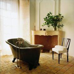 Salle de bain ancienne dans un château avec baignoire en zinc et cheminée