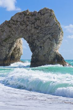 """Durdle Door, a natural limestone arch on the Jurassic Coast near Lulworth in Dorset, England : The name """"Durdle"""" is derived from the Old English """"thirl,"""" meaning bore or drill."""