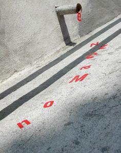 Enxurrada de letras (2004)  Bairro de Santa Tereza – Rio de Janeiro, RJ  Letras vinílicas coladas como se estivessem escorrendo dos escoadouros de muros e calçadas.