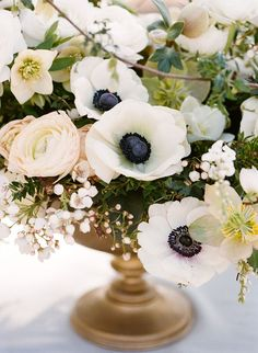 White and greenery arrangement with anemones in a gold container.