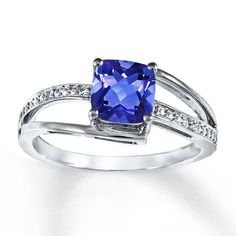 An elegant cushion-cut tanzanite shines while embraced by lustrous sterling silver in this ring for her. The exotic color is embellished with sparkling diamond accents.  Gently clean by rinsing in warm water and drying with a soft cloth.