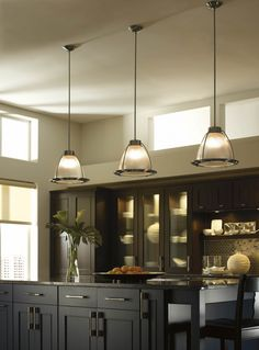 A popular way to highlight a kitchen island is to cluster multiple mini-pendants above it. Mix and match styles and finishes at differing heights for a contemporary feel. Or, line the island with the same size and style for a simple, clean-lined approach.