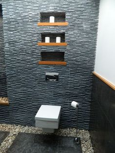 A very interesting Zen bathroom, with square minimal wall-hung toilet, and lovely niches with wooden shelves on the beautifully textured wall. Although this bathroom is minimal in terms of furniture and colours, it is very rich in texture. I love the stones on the floor, that act as a visual grout between the large floor tiles. And the horizontally textured wall behind the toilet is marvellous.
