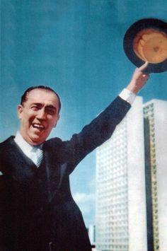 """9 — JK e a inauguração de Brasília (1960)        Fotografia feita em 21 de abril de 1960. Gervásio Baptista, repórter fotográfico da revista """"Manchete"""", tinha ido a Brasília com a missão de fazer a foto de uma edição especial sobre a inauguração da nova capital. A fotografia, na subida da rampa do Palácio do Planalto, com Juscelino Kubitschek acenando com a cartola correu o mundo e virou um dos símbolos da cidade. Fotografia: Gervásio Baptista."""
