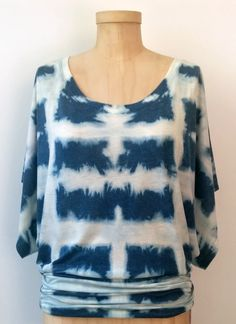 This cute indigo shibori dolman sleeve top is right on trend!  It's a size 2X and the fabric is a super soft jersey.  It was dyed with naturally derived indigo and then a discharge paste was applied with a shibori technique to obtain the design.  This top is easy care and machine washable.  Pair it with denim skinny jeans, a cute pair of capris, or a pencil skirt and you're good to go!  For more see www.flygurldesigns.etsy.com.