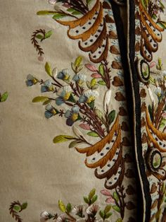 Detail embroidery, waistcoat, France, c. 1790. Cream silk satin, exquisitely embroidered with floral motifs in coloured silk, with linen back and fustian lining, short lining sleeves (added later).