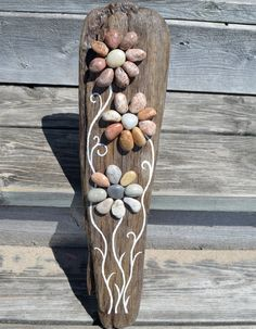 Awesome piece of Lake Huron driftwood, hand gathered by me along with all the pebbles used to create the flowers. A one of a kind piece for sure. It has a hook on the back for hanging purposes. Its been given a coat of varnish to seal and protect but will Not stand up to the elements year after year. Best kept under cover. This gem measures approx 18x4.5  Thanks so much for stopping by my shop, Jools  Overseas orders go by boat unless we double the shipping charges