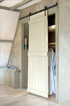 Deze kastruimte wordt afgesloten met een deur die werd gemaakt van oude dakspanten.