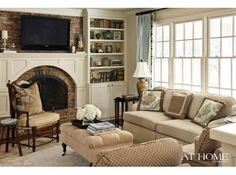 Cozy den by Krista Lewis. want for house The kitchen opens to a comfortable hearth room, where Lewis added a mantle to the original brick fireplace. A sofa from Cobblestone  Vine pairs with a Ballard Designs ottoman, and a Cobblestone  Vine velvet crewel pillows tops a Furniture Classics chair.