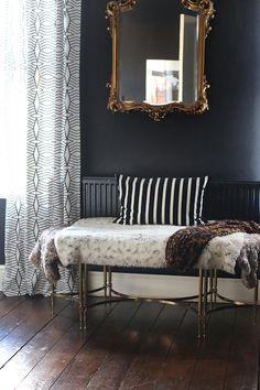 black bedroom with gold mirror and dark wood floors