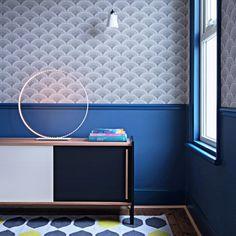 """Dans le bureau au soubassement bleu, une console noire et bois vintage, Atelier Rien à Cirer et du papier peint """"Feather Fan"""" Cole & Son. Le tapis Habitat rehausse le tout."""