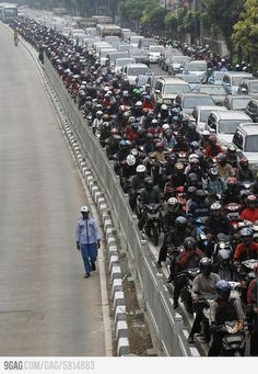 Hundreds of motorcyclists stuck in traffic jam and a man walking unaffected