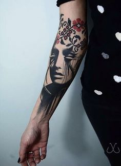 An interesting and abstract looking sleeve tattoo. The design starts off with pixel flowers above while transitioning to a woman with closed eyes below.
