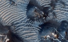 This colorful scene is situated in the Noctis Labyrinthus, perched high on the Tharsis rise in the upper reaches of the Valles Marineris can...