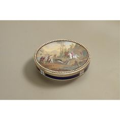 A PEARL, GOLD AND ENAMEL SNUFF BOX maker's mark partially rubbed but probably R crowned incuse, circa 1790  oval, the lid inset with a plaque painted with a wild boar hunt, split pearl border, the sides and base enamelled in translucent royal blue over engine-turning within paillon and white opaque enamel borders
