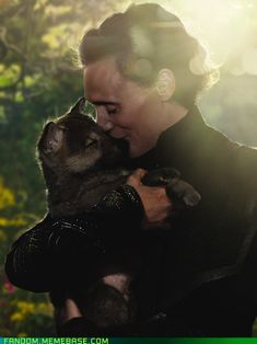 This is a picture of Loki holding a puppy. I think we can all now forgive him for destroying New York City and attempting to take over the world.