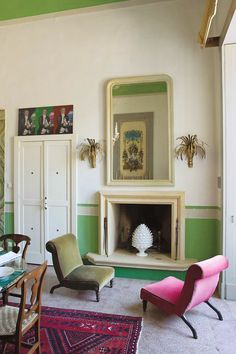 Pink and green colour velvet chairs look gorgeous on either side of this fireplace. Lovely vintage wall lights.
