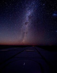 The Milky Way shines in all its majesty, as well as the Magellanic Clouds on the right. Some of the docking stations for the Auxiliary Telescopes of the VLTI lie in the foreground.