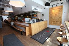 bar seating is space efficient and keeps the space casual. the menu on the wall should be simple yet appealing.