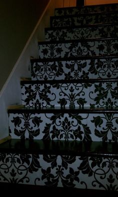 wallpapered the rise of the stairs! still have to finish painting the trim... More