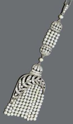 A BELLE EPOQUE DIAMOND AND PEARL PENDANT WITH CHAIN, ca. 1915. Enchanting pendant designed as a stylised tassel with a fine floral openwork asymmetric upper part set with diamonds, attached thereto on a moveable mount: 10 rows of probably Oriental pearls, above a decorative part of two corresponding openwork half-spheres set with diamonds, connected by 4 rows of pearls, mounted in platinum. #BelleEpoque #vintage #pendant