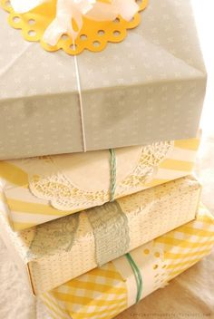 Gifts wrapped in yellow patterned papers, twine, doilies, etc... for decor. Can be used to add height to favor/cake table too.
