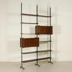 Libreria anni 50-60 ad elementi regolabili in altezza; legno impiallacciato palissandro, metallo laccato, puntali in ottone. Discrete condizioni; lucidatura da riprendere.