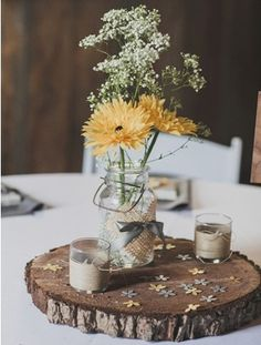 Rustic wedding centerpiece. Love the details ... daisy confetti sprinkled on the tree slab base and burlap heart on the mason jar.