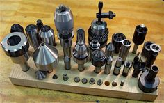 Lathe tailstock accessories in a red oak holder: MT3/ER40 collet chuck, bull nose live center, MT3 end mill holders, arbors, drill chucks, MT3/Taig accessories adapter, MT3 to MT2 adapter, live centers for wood, dead centers, die holders. Note that wooden tool holders draw moisture away from the metal parts but composite woods can cause rust.
