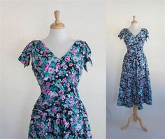 VINTAGE LANZ ORIGINALS COTTON SUMMER DRESS   This vintage dress is made in a floral cotton with petite flowers on a black background. The bodice of the dress has a V front and back, and vertical tucks in the front. The dress has a full back zipper and is sleeveless with a fabric epaulette tacked at the shoulder. The skirt is A cut and has two on-seam side pockets. A decorative cummerbund is attached at the waist giving the dress the appearance of a slightly dropped waist.    Item: Vintage…