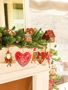 Detalle de repisa de la chimenea decorada con motivos navideños en verde y rojo