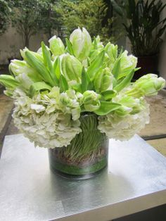 Green and white Parrot Tulips and Hydrangea in a glass cylinder vase with wheat grass and green sand on a metal table on a patio