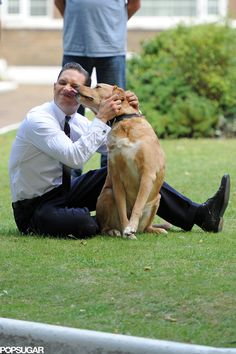 Tom Hardy playing with a dog on the set of Legend.