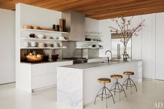 "The sleek, minimalist kitchen of author/photographer Kelly Klein complements the open and airy design of her Palm Beach, Florida, house, which was created by David Piscuskas of the firm 1100 Architect. ""Some people don't like looking at their things,"" Klein says of her kitchen's shelving. ""I like seeing my glassware and dishes."" (August 2012)"