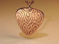 Swirling waves copper guitar pick pendant