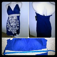 Cute Blue Sundress with Crochet Accents Dark blue dress with surplice neckline, built in bra cups, crochet trim at empire waist and straps,white raised print on front. Stretchy shirred back ensures a perfect fit. Fits up to size 16, comfortably. Soft, stretchy tshirt-like fabric. Print is slightly off center. Never worn. NWT. Just Love Dresses