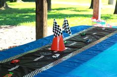 Table decor using plastic table cloths and tape at a Hot Wheels birthday party