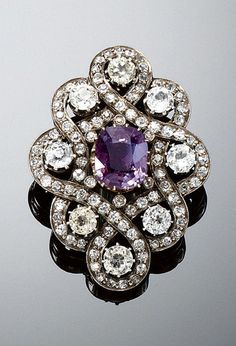 ALEXANDRITE BROOCH, LATE 19TH CENTURY. Set at the centre with a cushion-shaped alexandrite weighing 3.67 carats, within an interlacing surround of circular-cut diamonds and eight synthetic stones.