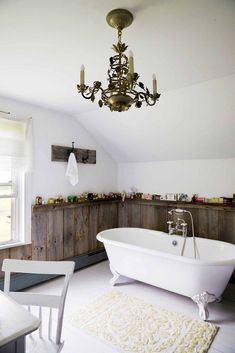 Rustic bathroom with wood and white walls, a chandelier, and a clawfoot bathtub