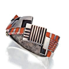 SILVER AND LACQUER BANGLE-BRACELET, JEAN DUNAND, CIRCA 1924.    The front composed of square and rectangular plaques applied with black and coral lacquer, internal circumference 6¼ inches.
