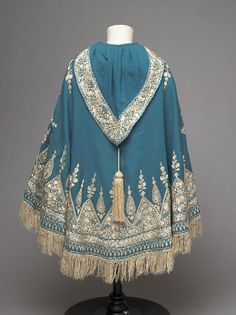 Child's cape.  Twilled peacock blue woollen cloth, embroidered in cream silk thread, with a cream tassel on the hood; Anglo-Indian ?, 1860-70