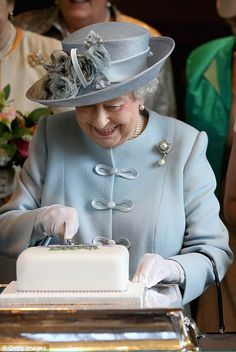 Doing it justice: The Queen beams as she cuts into the cake during the WI's Centenary Annual Meeting