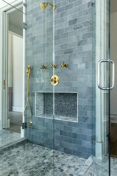 His and her seamless glass doors opens to a walk-in shower fitted with gray marble hex floor tiles and gray marble subway tiles fixed framing a gray mosaic tiled niche.
