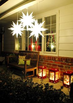 Christmas porch decoration... 3 stars hung at different heights and bright red lanterns lanterns with a strand of white lights in each... very much my taste!